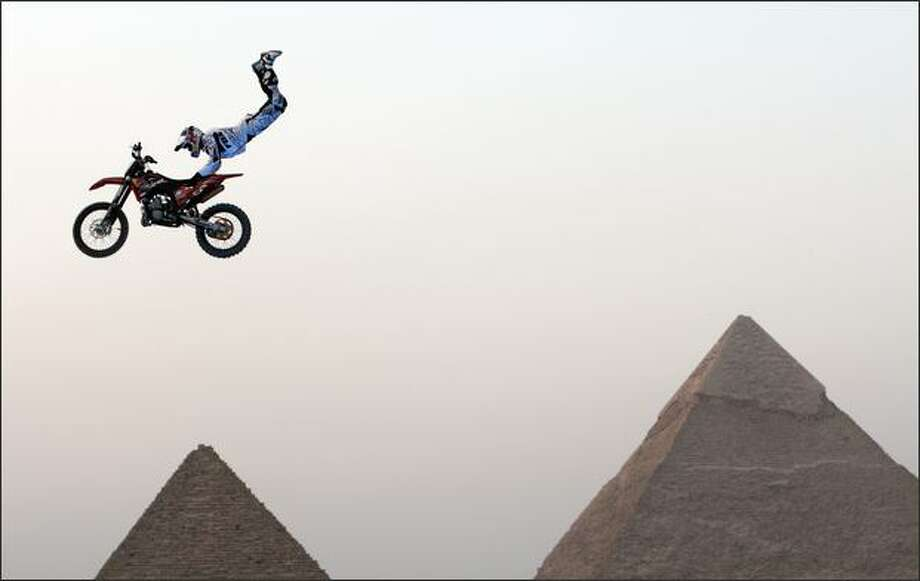 A biker performs in front of the Great Giza pyramids during Red Bull Fighters International Freestyle Motocross 2009 Exhibition Tour on the outskirts of Cairo. (REUTERS/Goran Tomasevic) Photo: Getty Images