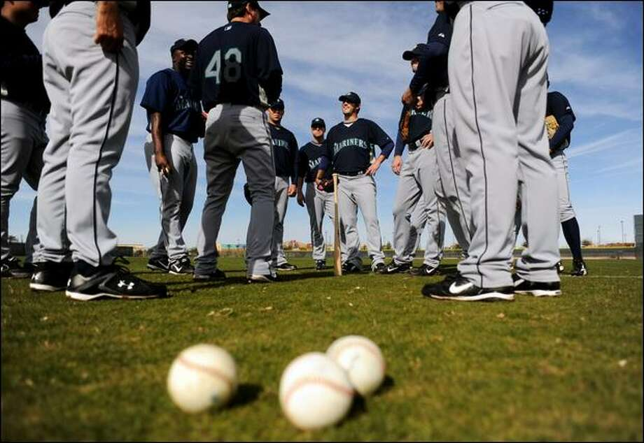 Mariners pitchers and catchers gather on the field Sunday during the second day of their spring training in Peoria, Ariz. The rest of the team reports Tuesday. Photo: Amanda Voisard/Special To The P-I