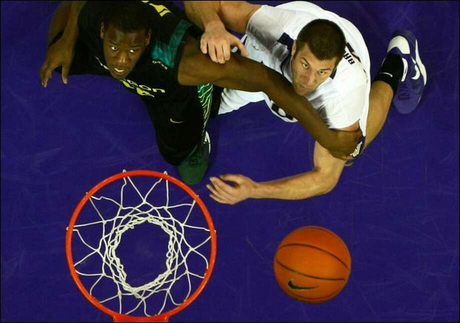 Oregon's Josh Crittle tries to hold off Jon Brockman in a battle for the ball in Saturday's Pac-10 game at Hec Ed Pavilion. Brockman had 18 rebounds, Crittle two in the Huskies' 103-84 win. Photo: Joshua Trujillo/Seattle Post-Intelligencer