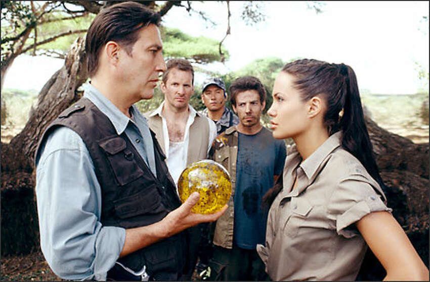 The villainous Jonathan Reiss (Ciarán Hinds) confronts Lara Croft (Angelina Jolie), her butler, Hillary (Christopher Barrie) and her assistant, Bryce (Noah Taylor).
