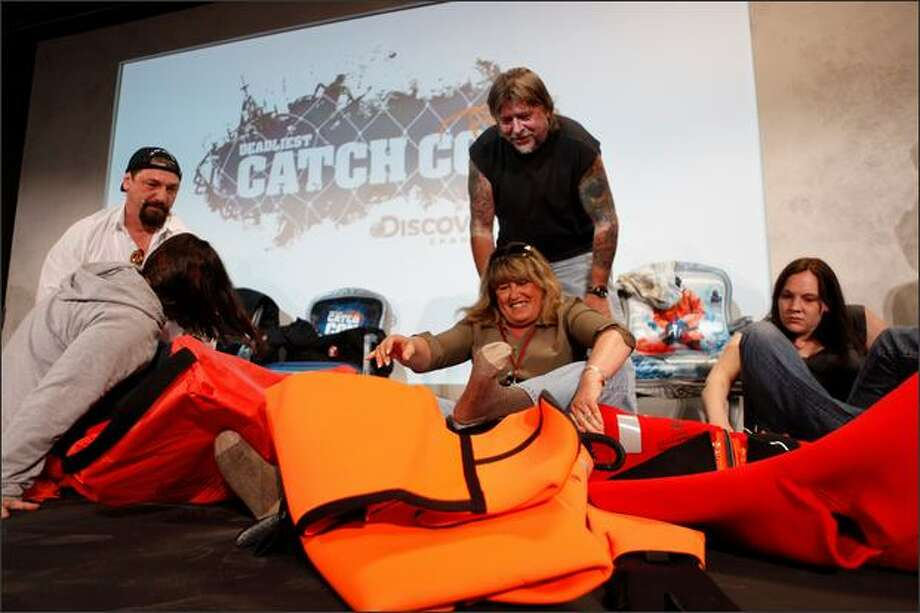 Ship captains Johnathan Hillstrand and Phil Harris help fans into survival suits in a speed dressing competition during CatchCon at the Bell Harbor Conference Center on Saturday in Seattle. (Thom Weinstein/Seattlepi.com)