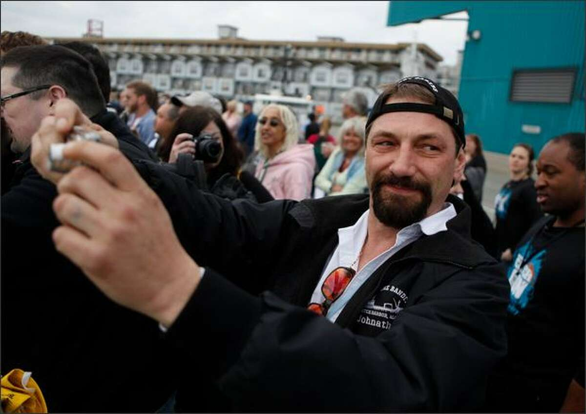FILE - Captain Johnathan Hillstrand, of the Time Bandit, takes time to enjoy the U.S. Coast Guard demonstration during CatchCon outside the Bell Harbor Conference Center in Seattle.