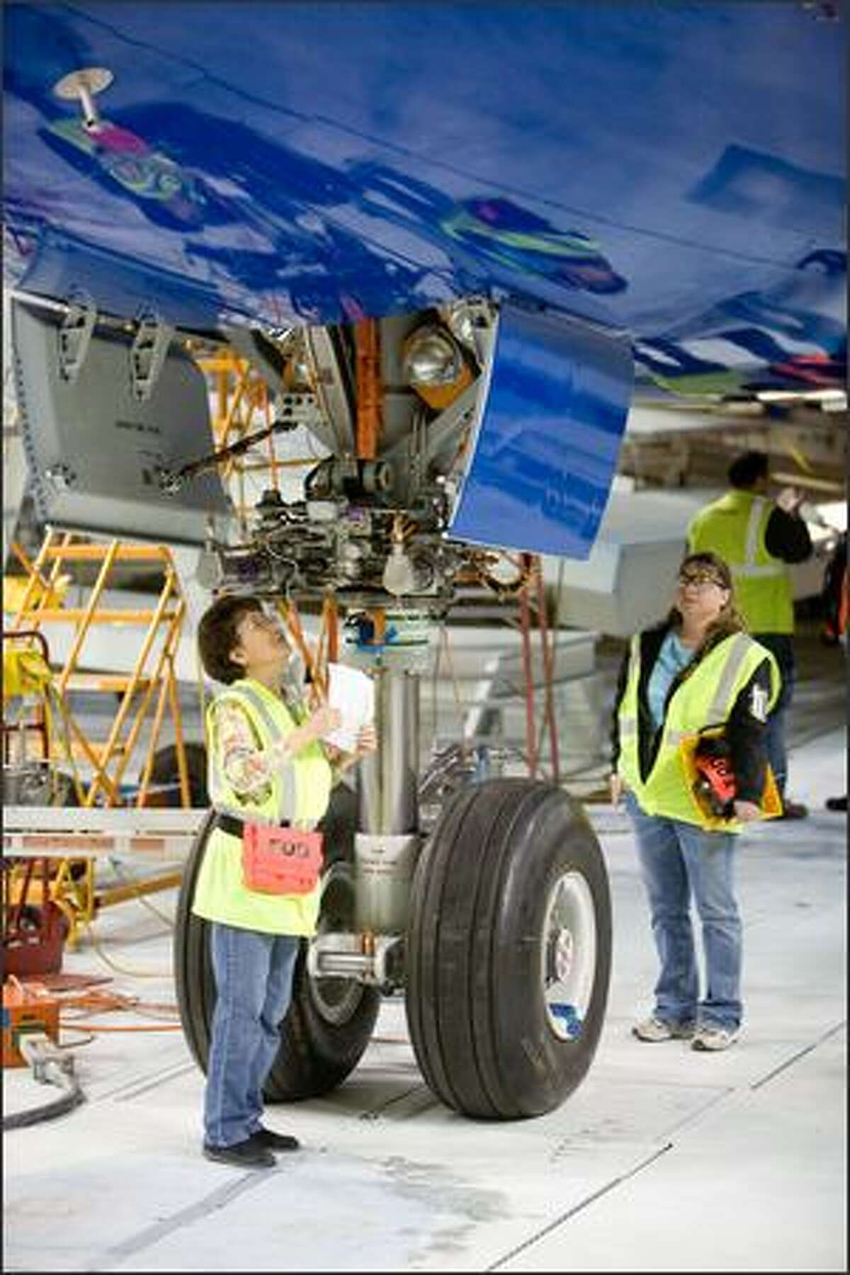 Workers, including Hui San Pang, left, test components of Boeing's first 787.