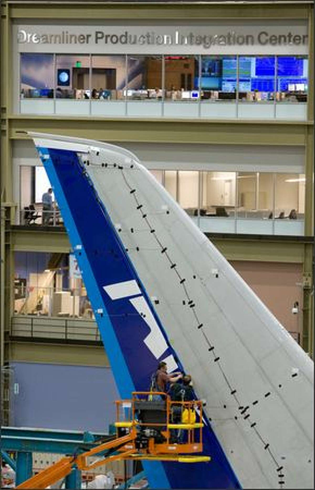 Workers attach parts to the tail of a Boeing 787.