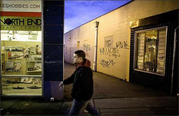A pedestrian passes graffiti at Toyoda Sushi, one of many Lake City businesses facing increased crime. An increase in gang activity and crime in the neighborhood has officials worried. Photo: Joshua Trujillo/Seattle Post-Intelligencer