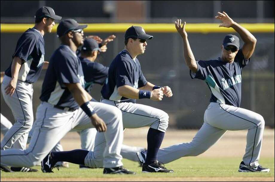 Adrian Beltre, right, leads a stretching drill during the Mariners' first full-squad workout of spring training Wednesday in Peoria, Ariz. Photo: Charlie Riedel/Associated Press