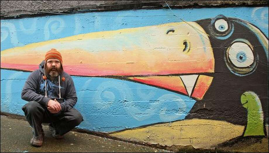 "One of muralist Ryan Henry Ward's many pieces across the city can be found on a wall near The Orange Splot Gallery in Fremont. ""I think his art has soul,"" gallery owner Kevin McKouen says. Photo: Mike Kane/Seattle Post-Intelligencer"