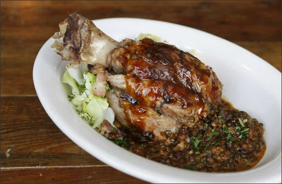 A braised pork shank is the picture of moist succulence with the bone taking up a great deal of space on the large place beside lentils and braised cabbage peppered with crispy bits of bacon. Photo: Meryl Schenker/Seattle Post-Intelligencer