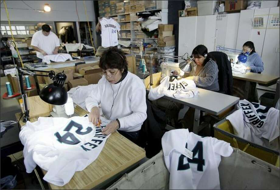 Workers at STT Sports Lettering Co. in Seattle, including Rosa Maria, foreground, produce Ken Griffey Jr. jerseys for the Mariners on Thursday. Photo: / Associated Press