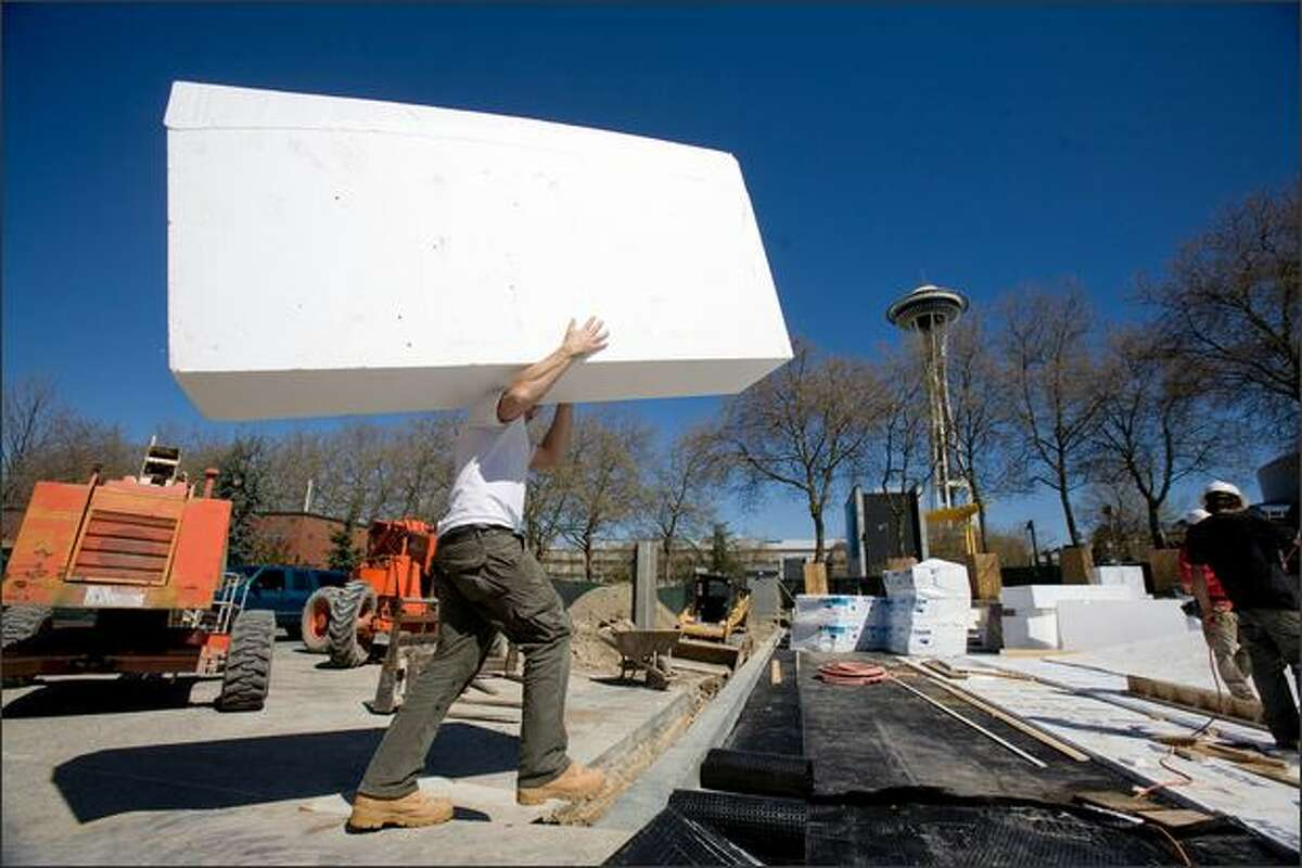 A worker carries a giant piece of plastic foam April 24 that will become part of the new Seattle Center Skate Park in Seattle.