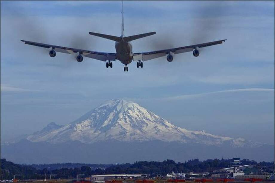 With Mount Rainier as a backdrop, a Boeing 707 Omega tanker does a fly-by at Boeing Field at 7:07 p.m. before landing.  (Photograph by Grant M. Haller 7/07/2007) Photo: P-I File