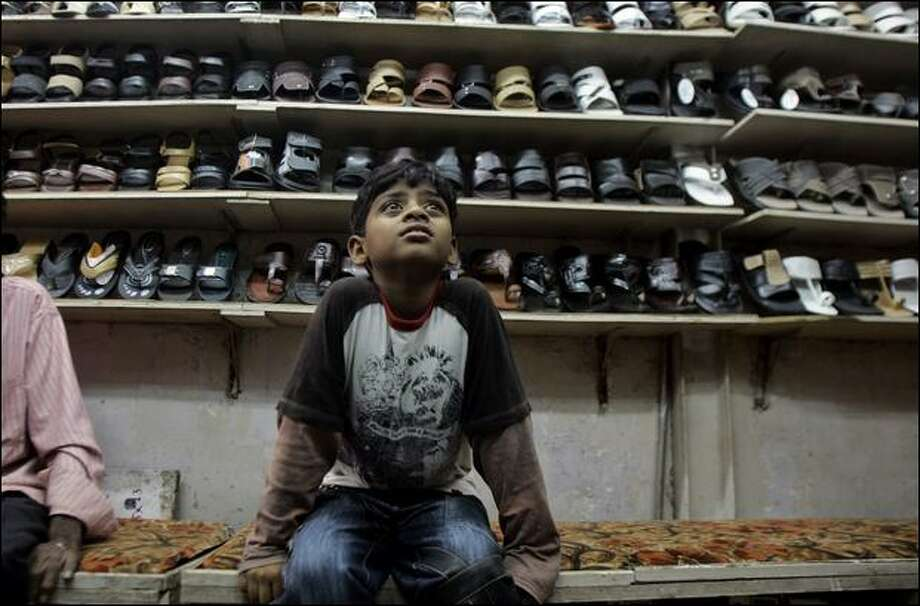 Azharuddin Ismail shops for shoes in Bandra, suburban Mumbai. The 10-year-old was cast as the hero Jamal Malik's brother Salim. His mother is traveling with him to the Oscars. Photo: Rajanish Kakade/Associated Press