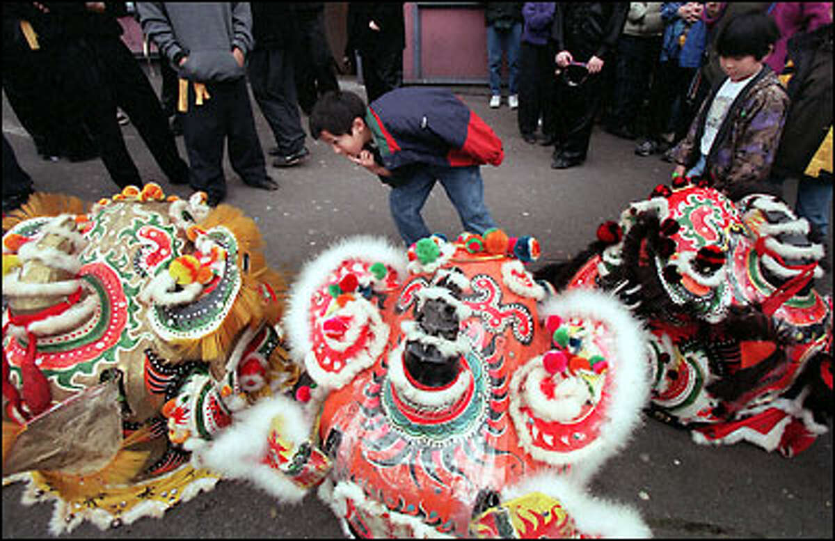 """""""It doesn't really bother me,"""" said 8-year-old George Rowe, center, of the noise from firecrackers at the Chinese Lunar New Year celebration yesterday in the International District. Also inspecting the mask, at right, is George's friend 7-year-old Chloe Choi. Both children were adopted, and their new parents want to provide cultural experiences from the children's roots."""