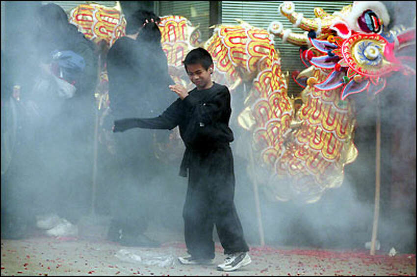 Chris Chu Jr., 8, makes a dash away from the smoke of firecrackers in Seattle's International District during the Chinese New Year celebration for the Hop Sing Tong organization last Tuesday.