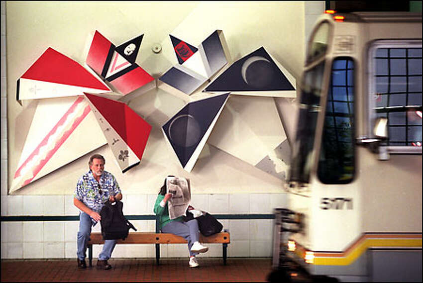 Riders at the International District station of the Metro bus tunnel wait below Sonya Ishii's steel origami sculptures, examples of public art.