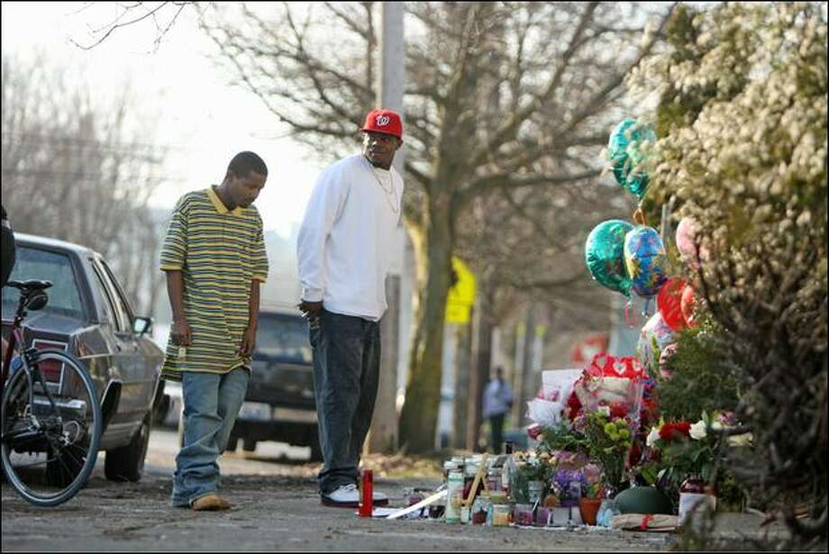 "Sean Jones, left, and Larry Hutchinson visit a memorial for Love, a friend they'd had since boyhood. Love, who participated in several rallies against youth violence, was shot to death Monday. ""It's a shame that this could happen to such a good person,"" Jones said."