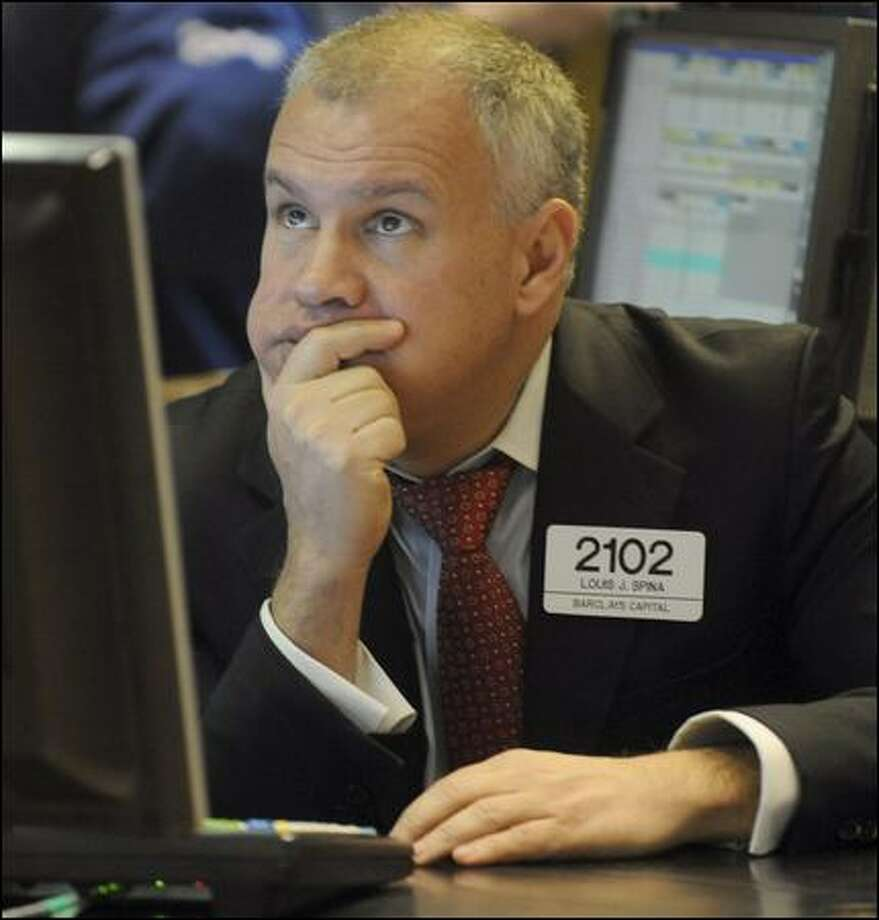 Louis Spina of Barclays Capital spends a tough day Friday at the New York Stock Exchange. Photo: Henny Ray Abrams/Associated Press