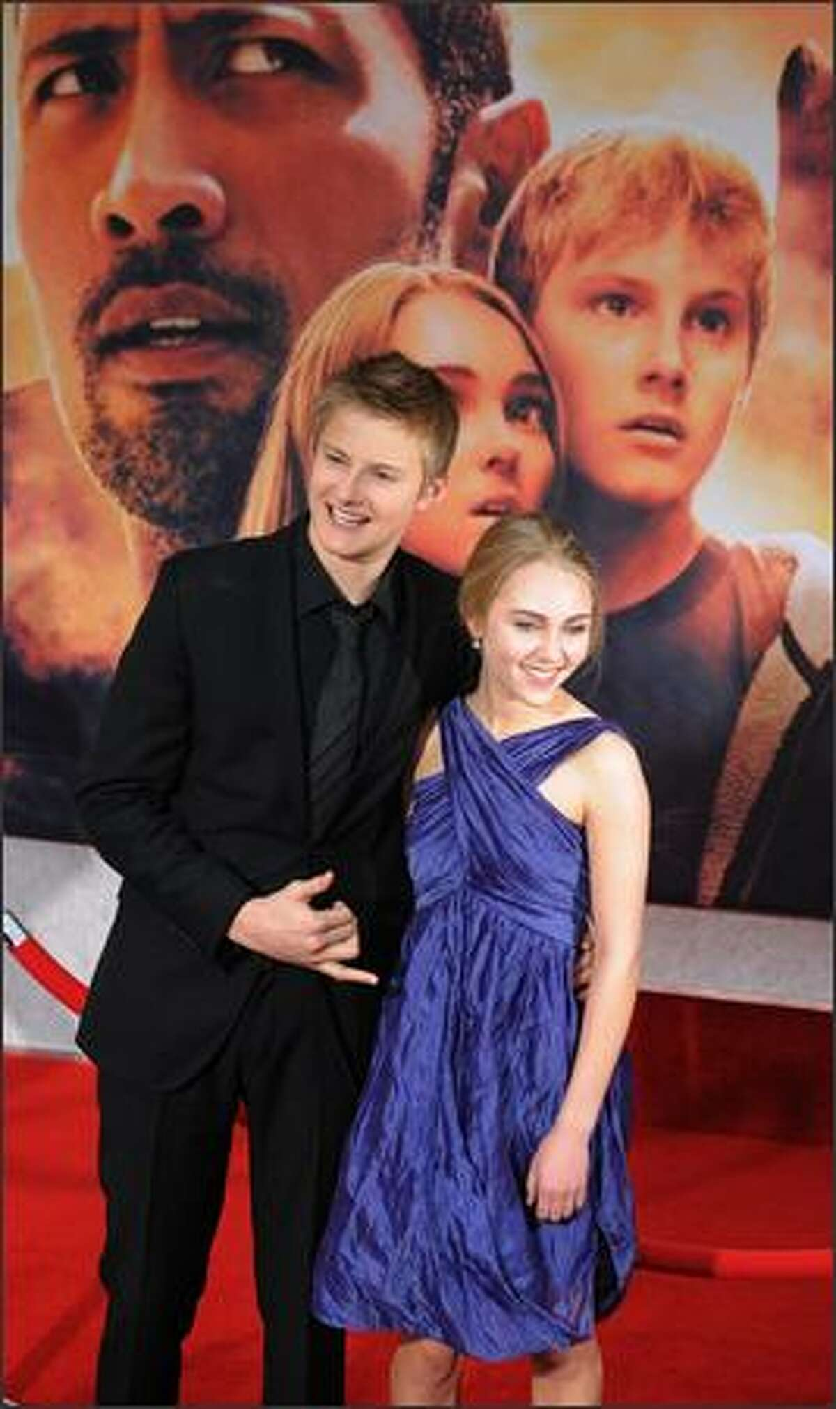 Actor Alexander Ludwig and co-star AnnaSophia Robb pose for photos as they arrive for the world premiere of the Disney film