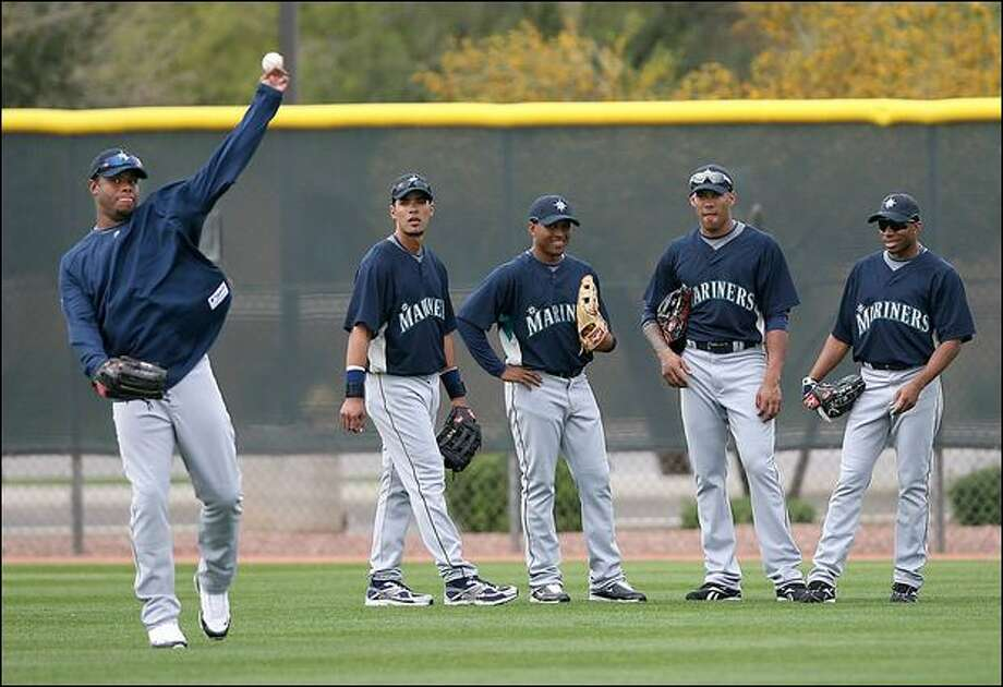 "From left, outfielders Franklin Gutierrez, Freddy Guzman, Greg Halman and Endy Chavez watch as Ken Griffey Jr. throws a ball during drills Sunday. It was the first team workout for Griffey since he re-signed with the Mariners. ""I feel like I'm on a darn high school recruiting trip,"" Griffey, 39, joked. Photo: Scott Eklund/Seattle Post-Intelligencer"