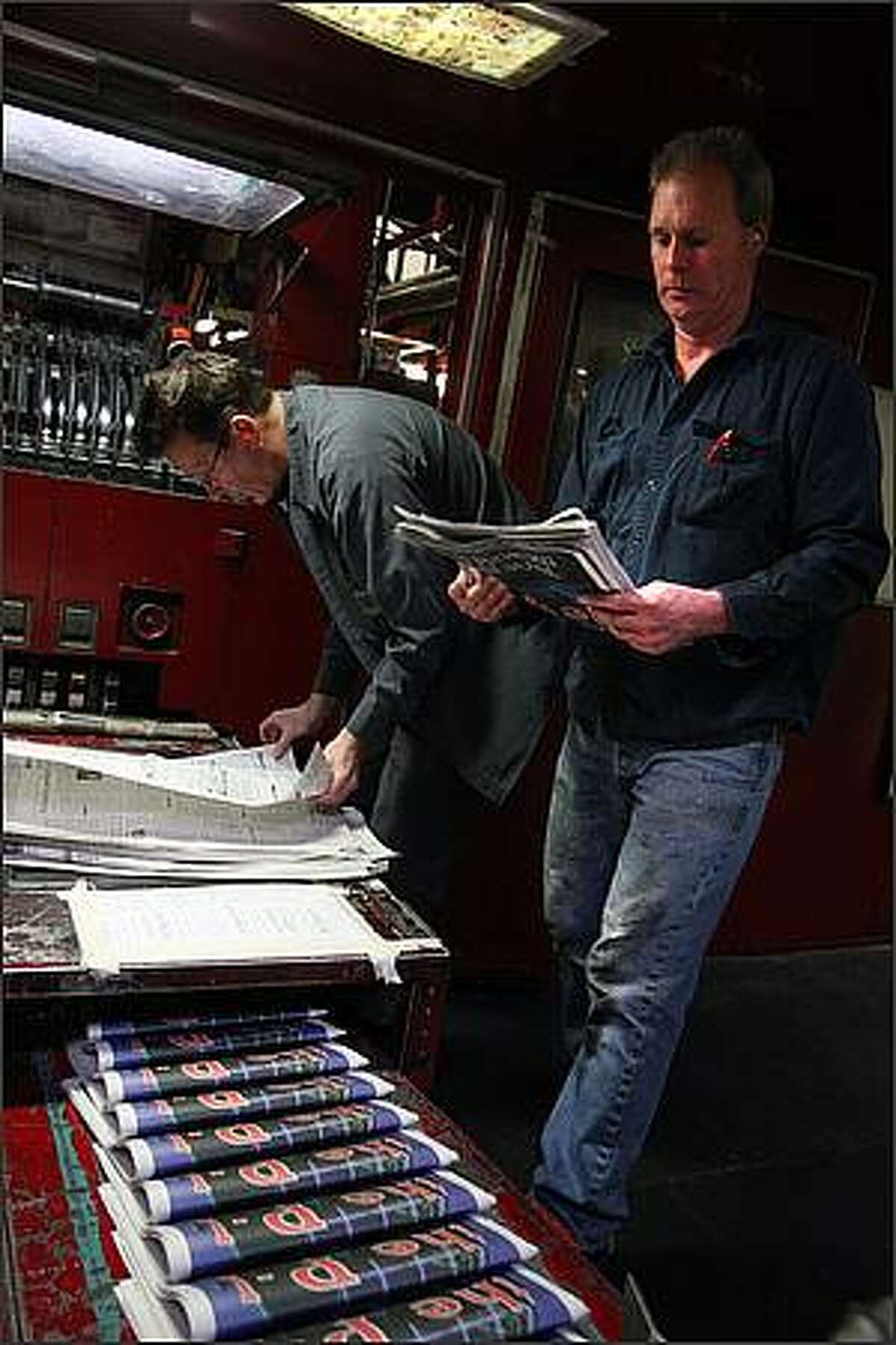 Lead Press Operator Michael Klop adjusts the folder settings so everything lines up at the start of the run while Ed Harding (right) check the front page color of the final edition of the Seattle Post-Intelligencer at the Seattle Times North Creek facility in Bothell, Washington on March 16, 2009. The Seattle Post Intelligencer has been publishing since 1863.