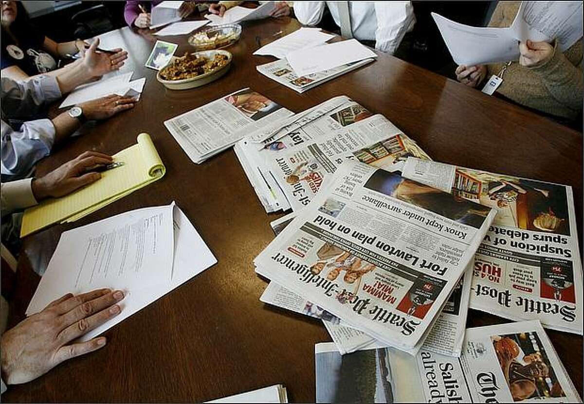 Papers lie on the newsroom conference table during the morning news meeting, after it was announced that Tuesday's paper will be the final print edition of the Seattle Post-Intelligencer.
