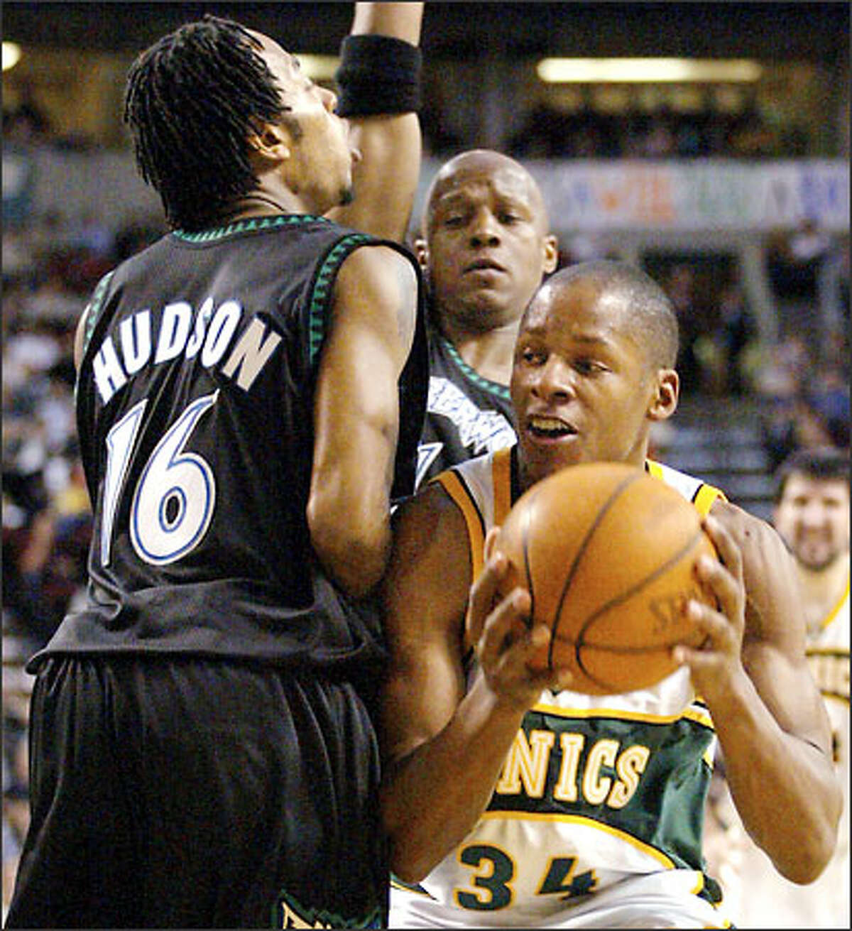 Sonics guard Ray Allen drives past the Timberwolves' Anthony Peeler and Troy Hudson last night. Allen led all scorers with 33 points.
