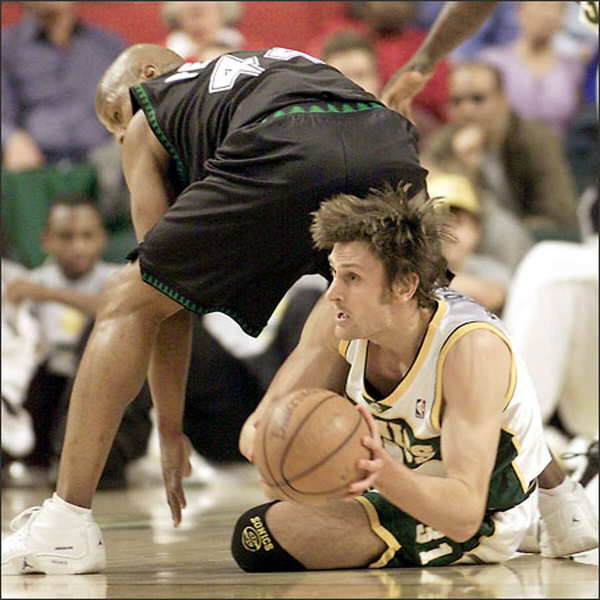 Sonics guard Brent Barry, behind Minnesota's Anthony Peeler, comes up with a loose ball in the first quarter.