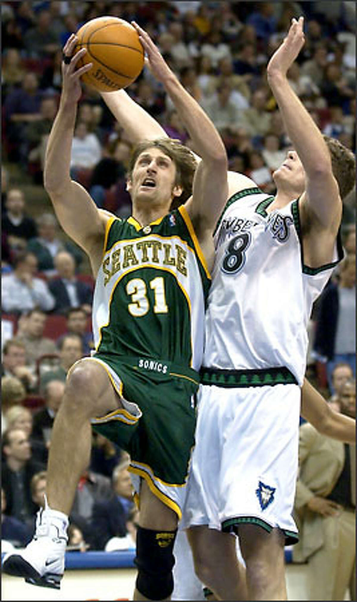 Brent Barry goes up for a shot against Timberwolves center Radoslav Nesterovic. Barry scored 11 points in 32 minutes.
