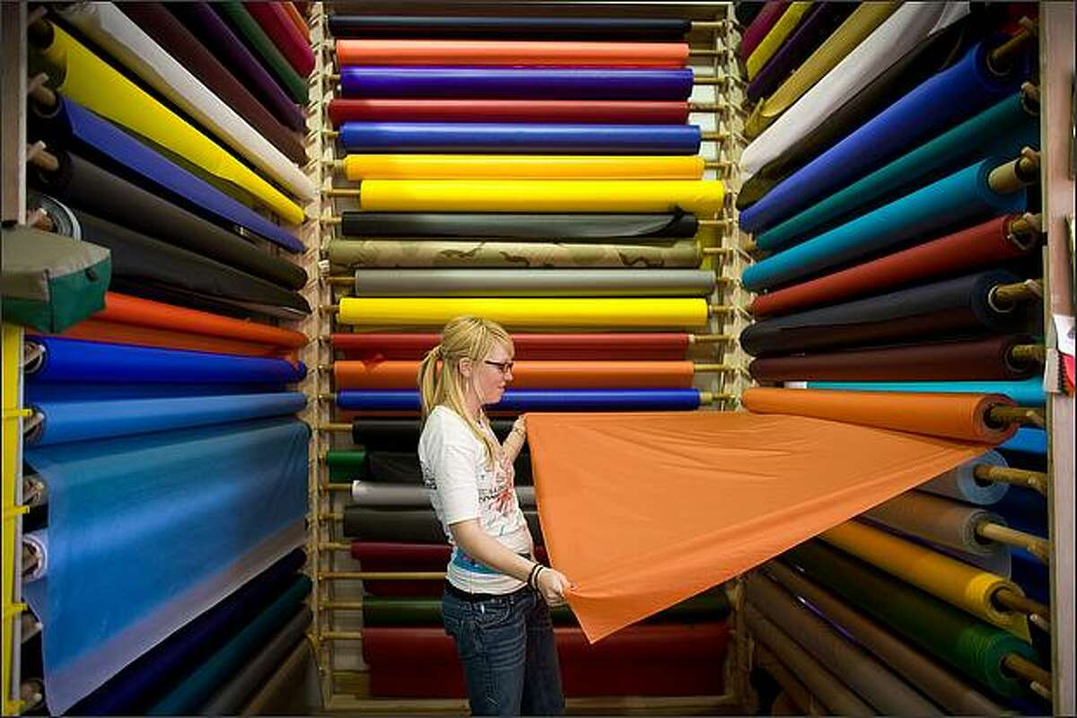 Sarah Crane, an employee of Seattle Fabrics, pulls out a roll of rip-stop nylon at the outdoor fabric store on Aurora Avenue North.