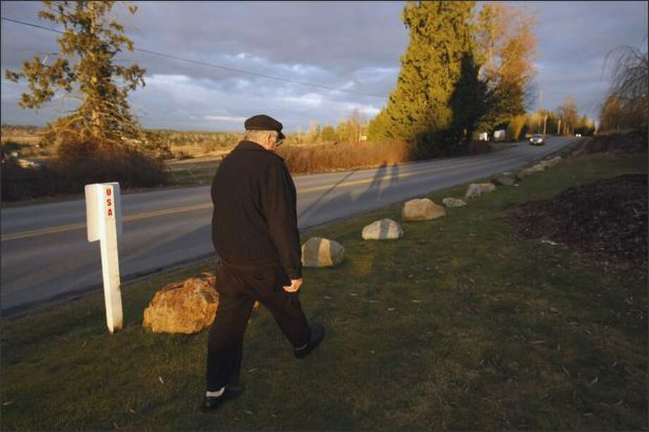 Bob Boulé, who owns Smuggler's Inn in Blaine, walks along his property. The large rocks mark the border and the Canadian road is named 0 Avenue. Sensors in the ground go off when someone crosses the border. Photo: Meryl Schenker/Seattle Post-Intelligencer