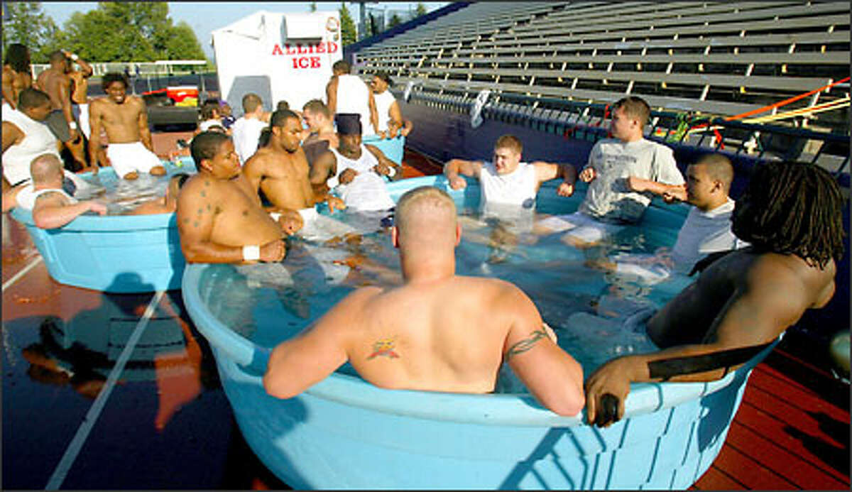 UW players cool off after practice in tubs filled with ice and water.