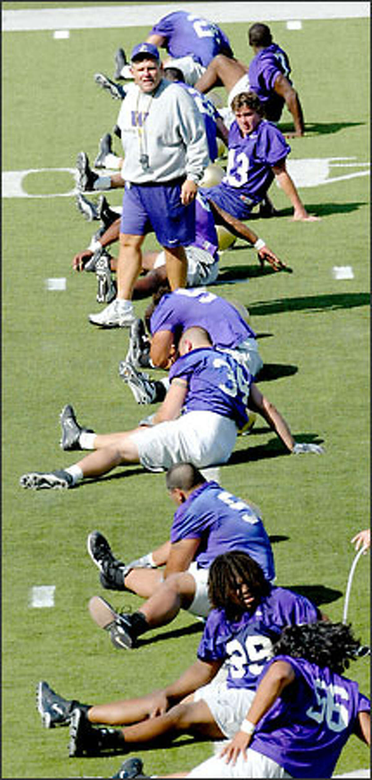 Keith Gilbertson oversees a line of players stretching at his first practice as University of Washington head football coach. The Huskies open their season Aug. 30 at Ohio State.