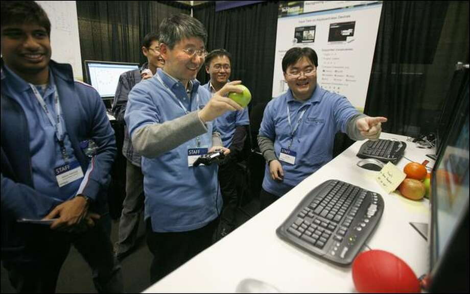 Qiang Huo, center, and Lei Ma, right, Microsoft researchers from the Beijing office, use an apple to demonstrate writing Chinese characters in the air. Photo: Paul Joseph Brown/Seattle Post-Intelligencer