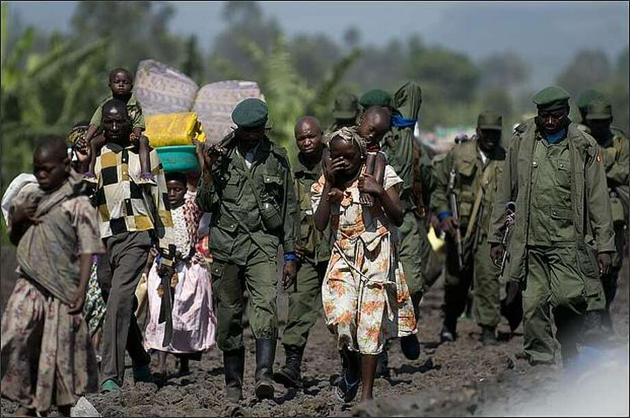 Democratic Republic of Congo soldiers and Internally Displaced People march into the provincial capital of Goma, on October 29, 2008. Thousands of Congolese people arrived into Goma from the Kibati provisional camp where they arrived on Oct 27 after violence started between Forces loyal to renegade Laurent Nkunda and the Congolese army. Goverment forces are fleeing from the key eastern Democratic Republic of Congo city of Goma ahead of advancing rebels, military sources and residents said today. AFP PHOTO/Walter ASTRADA