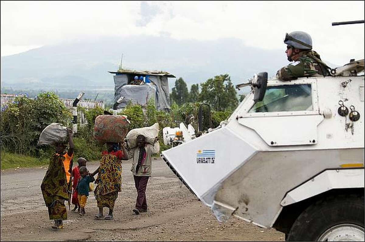 A group of Internally Displaced Congolese People walk in front of an UN armored vehicle in the provincial capital of Goma, on October 30, 2008. Congolese rebels closed in on this strategic eastern city sparking chaos as government forces, residents and tens of thousands of refugees scrambled to leave. The UN Security Council late Wednesday slammed the rebel push toward the provincial capital and expressed alarm at reports of heavy weapons fire across DR Congo's border with Rwanda. AFP PHOTO/Walter ASTRADA