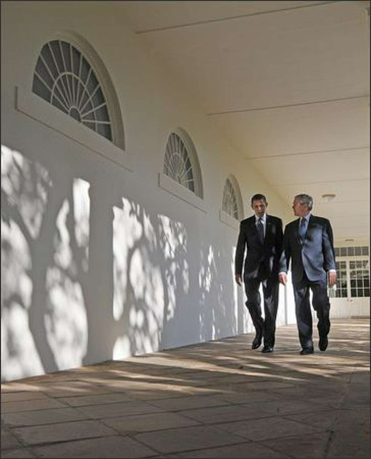 President George W. Bush and President-elect Barack Obama walk through the colonnade on Monday to the Oval Office at the White House in Washington, D.C.