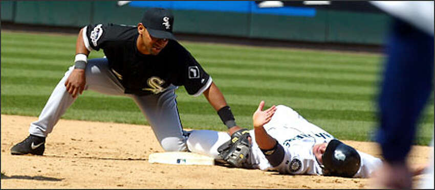 The Mariners' Bret Boone slides safely past the tag of White Sox second baseman D'Angelo Jimenez during the sixth inning.