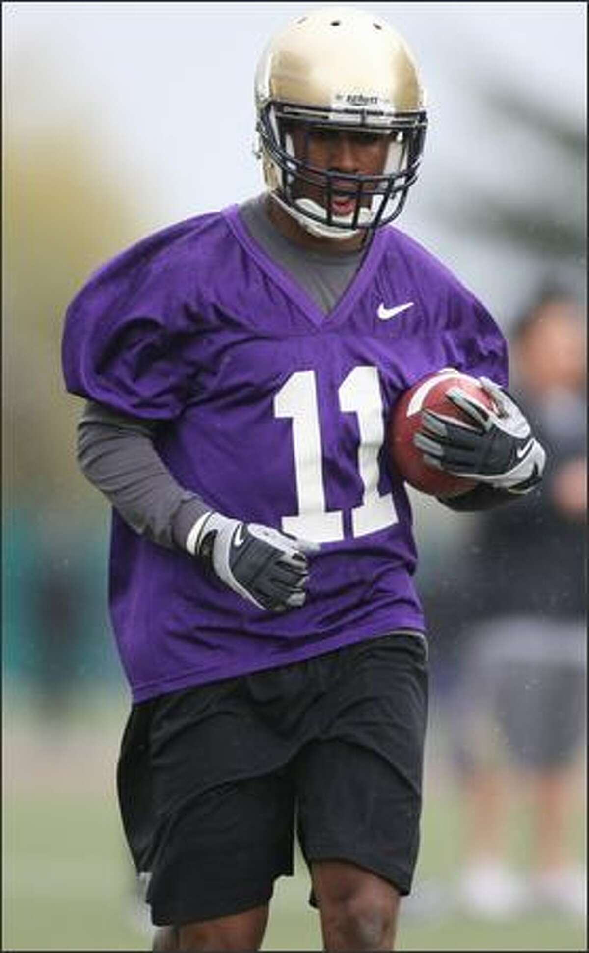 Junior D'Andre Goodwin runs with the ball during the Huskies' first season practice.