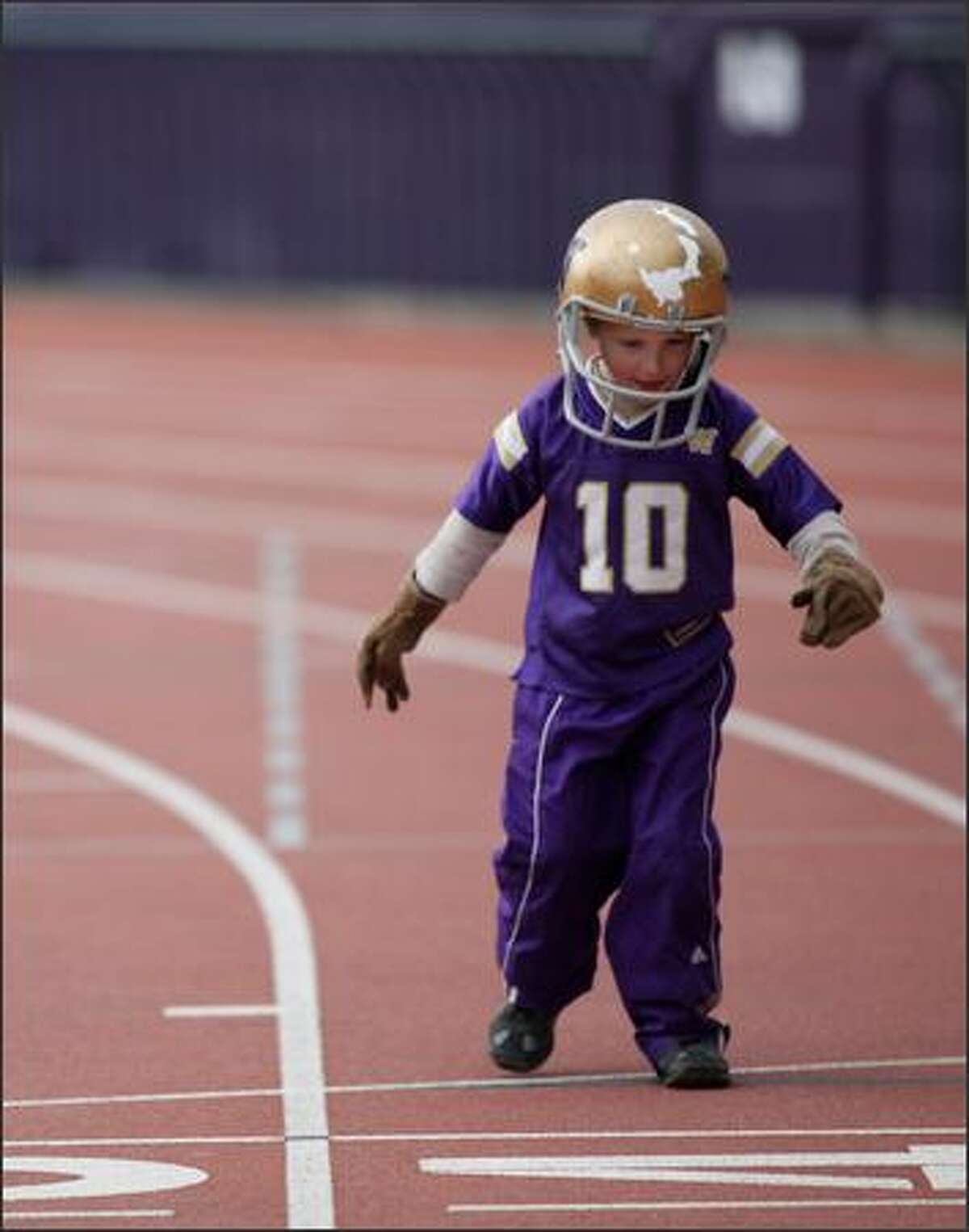Axel Johnson, son of Darin Johnson, plays around on the track while the Huskies practice.