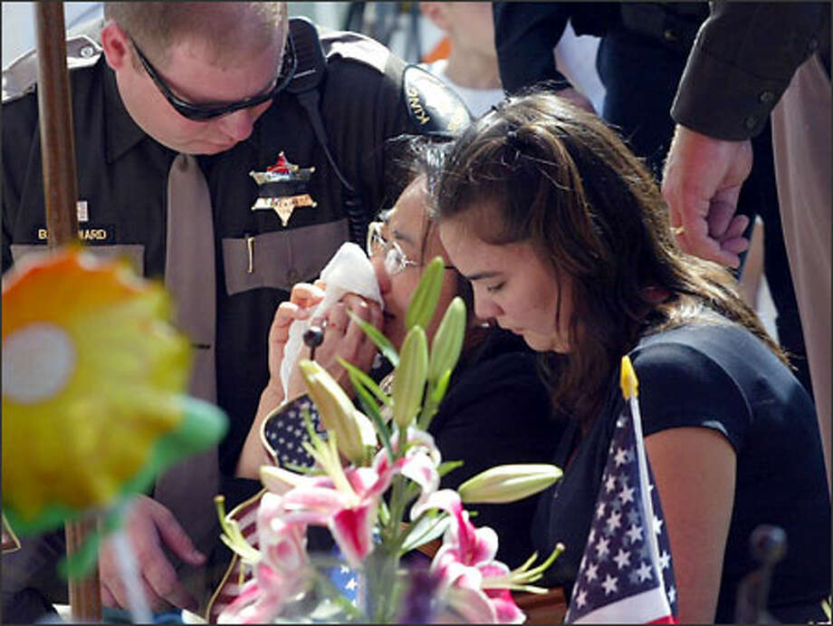 An emotional Sun Herzog, center, visits a roadside memorial for slain Federal Way Police Officer Patrick Maher. Herzog's husband, King County Sheriff's Deputy Richard Herzog, was killed in the line of duty last year. Photo: Gilbert W. Arias, Seattle Post-Intelligencer