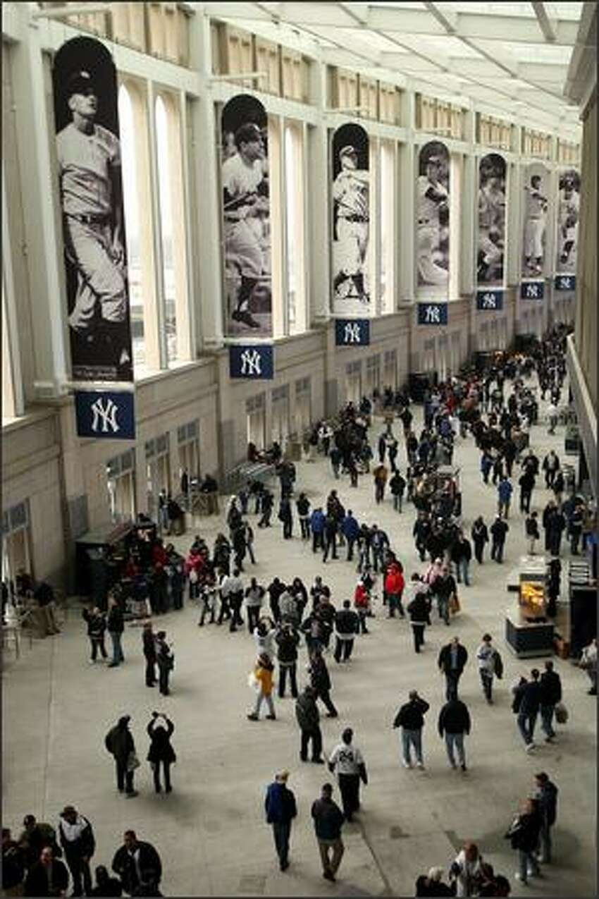Spectators walk through the Great Hall of the new Yankee Stadium before the New York Yankees' exhibition game against the Chicago Cubs on Friday in the Bronx borough of New York. The game marked the first time the Yankees played in their new ballpark.