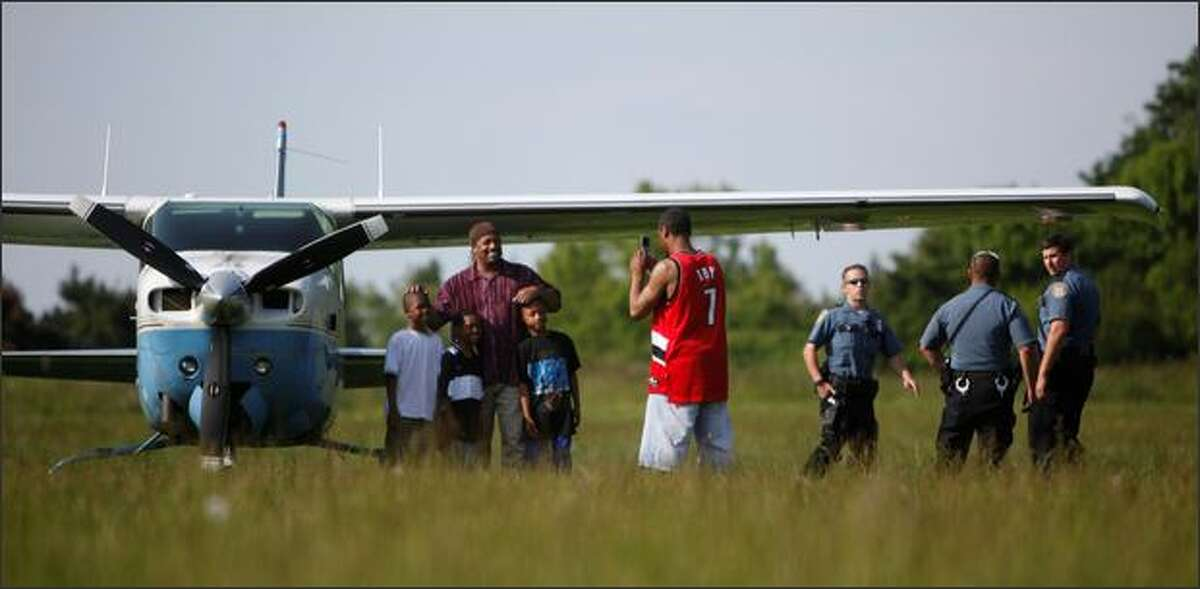 Russell Hebert Jr., center in red, takes a photo of his family with the plane in the background. The Cessna made an emergency landing Monday at Genesee Park.
