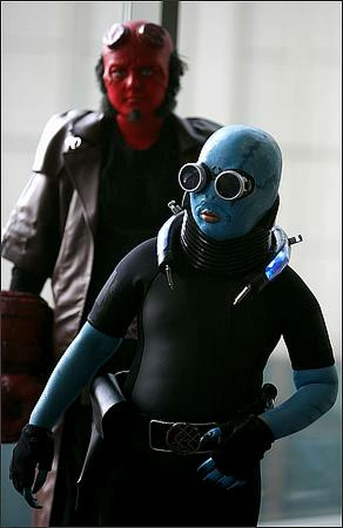 Cameron Hudson, 9, dressed as Abe Sapien, and his brother Carson, 11, dressed as Hellboy, walk the halls of the Emerald City ComiCon.