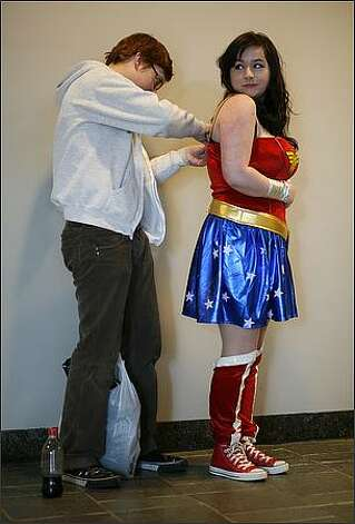 Wonder Woman, aka Kaza Ayersman of Tacoma, gets costume help from Robbie Specht. Photo: Joshua Trujillo, Seattlepi.com