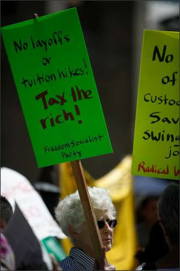 Protesters hold signs in Red Square during a rally against budget cuts and custodial swing shift eliminations at the University of Washington in Seattle, Wash. (May 28, 2009) Photo: Clifford DesPeaux, Seattlepi.com