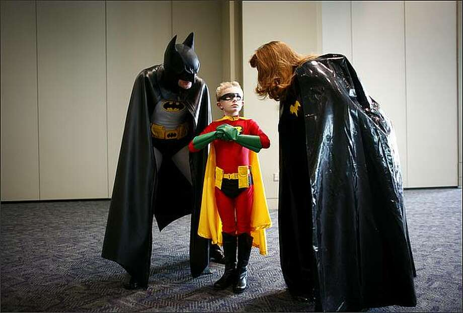 Mark VanDoornik, 7, dressed as Robin, gets some parental advice from his dad Don, dressed as Batman, and mom Mary Anne, dressed as Batwoman, at the Emerald City ComiCon on Saturday at the Washington State Convention & Trade Center in Seattle. Photo: Joshua Trujillo, Seattlepi.com
