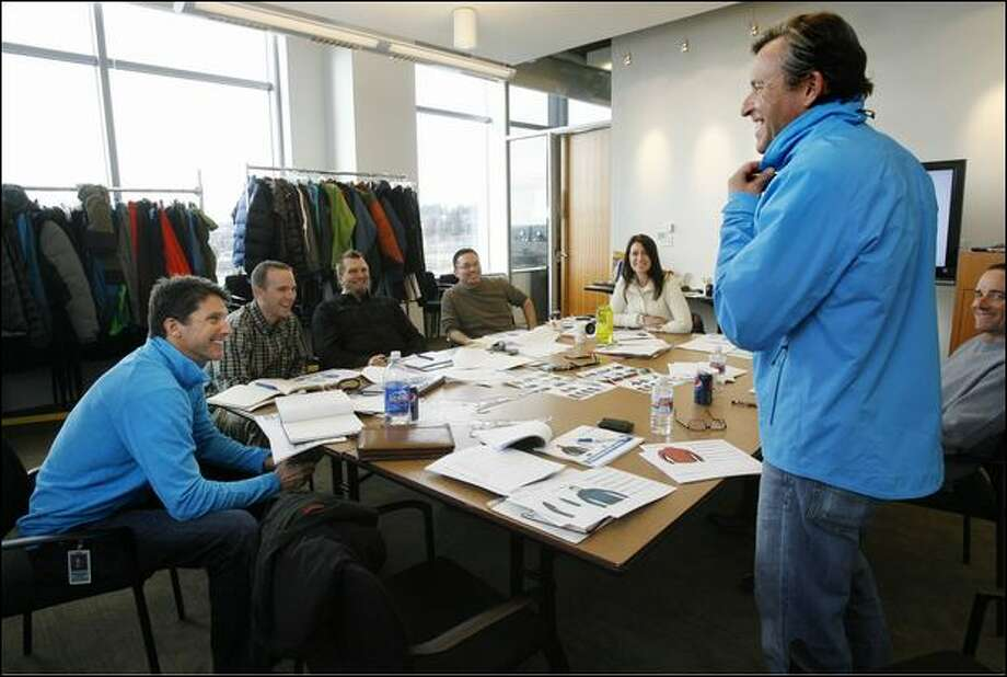 Mountain climber Ed Viesturs, second right, tries on a prototype of the FirstAscent midnight lite jacket Thursday as fellow climber Peter Whittaker, left, and others watch during a design team meeting at Eddie Bauer headquarters in Bellevue. Photo: Dan DeLong/Seattle Post-Intelligencer