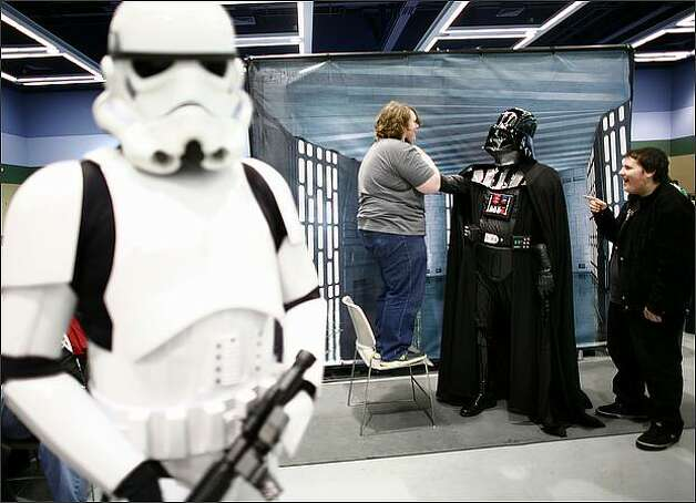 "Michael Paulin of Everett is ""choked"" by the evil Darth Vader, aka Marc Semenchule, as his friend Daniel Doughty, right, finds mirth in the scene at the Emerald City ComiCon. Photo: Joshua Trujillo, Seattlepi.com"