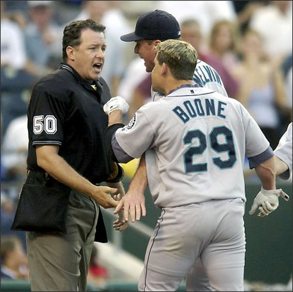 Mariners second baseman Bret Boone (29) and manager Bob Melvin argue with umpire Paul Emmel after Boone was ejected in the first inning against the Kansas City Royals. Boone, who struck out to end the inning, was ejected after he threw his bat and helmet while leaving the plate.