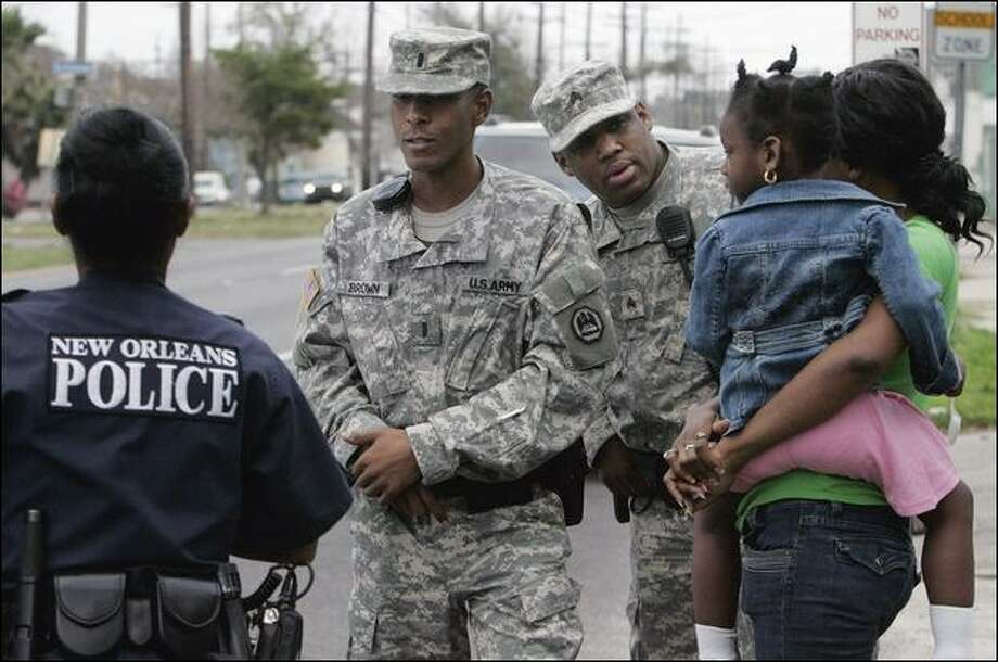 Louisiana National Guard Lt. Ronald Brown Jr., second left, and Sgt. Wayne Lewis work with a police officer on a call Thursday in New Orleans. Troops are leaving the city Sunday. Photo: Bill Haber/Associated Press